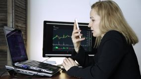 Θηλυκός έμπορος που μιλά στο τηλέφωνο και το διάγραμμα ανταλλαγής νομίσματος προσοχής στο όργανο ελέγχου υπολογιστών Εργασία για  απόθεμα βίντεο