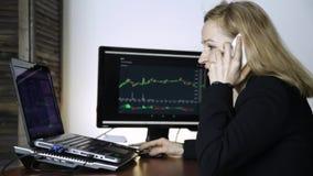 Θηλυκός έμπορος που μιλά στο τηλέφωνο και το διάγραμμα ανταλλαγής νομίσματος προσοχής στο όργανο ελέγχου υπολογιστών Εργασία για  φιλμ μικρού μήκους