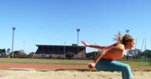 Θηλυκός αθλητής που ασκεί το μακροχρόνιο άλμα στον αθλητικό τόπο συναντήσεως 4k φιλμ μικρού μήκους
