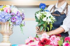 Θηλυκός ανθοκόμος στην εργασία που χρησιμοποιεί την τακτοποίηση κάνοντας την όμορφη τεχνητή ανθοδέσμη να περιβάλει στο ανθοπωλείο στοκ φωτογραφία