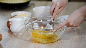 Θηλυκός αρχιμάγειρας που χτυπά ελαφρά τα αυγά στο κύπελλο γυαλιού στον πίνακα κουζινών φιλμ μικρού μήκους