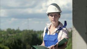 Θηλυκός αρχιτέκτονας μηχανικών κατασκευής με τα έγγραφα σε ένα εργοτάξιο οικοδομής απόθεμα βίντεο