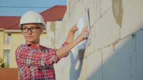 Θηλυκός αρχιτέκτονας που διαβάζει ένα στρέθιμο της προσοχής σε ένα εργοτάξιο οικοδομής νέοι επιτυχείς επαγγελματίες στοκ εικόνα με δικαίωμα ελεύθερης χρήσης