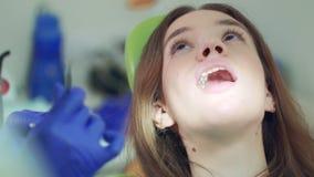 Θηλυκός ασθενής στην αναθεώρηση οδοντιάτρων στην κλινική Επεξεργασία δοντιών στο γραφείο οδοντιάτρων απόθεμα βίντεο