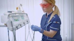 Θηλυκός γιατρός με τα προστατευτικά γυαλιά και το τρυπάνι χεριών φιλμ μικρού μήκους