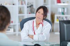 Θηλυκός γιατρός που ακούει το γραφείο patientin στοκ φωτογραφία