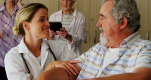 Θηλυκός γιατρός που γονατίζει μιλώντας στο με ειδικές ανάγκες ανώτερο άτομο στην αναπηρική καρέκλα 4k απόθεμα βίντεο