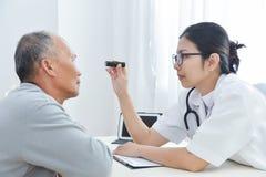 Θηλυκός γιατρός που ελέγχει στα ανώτερα υπομονετικά μάτια ατόμων Στοκ Εικόνα