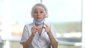 Θηλυκός γιατρός που ορίζει το πακέτο των χαπιών φιλμ μικρού μήκους