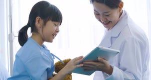 Θηλυκός γιατρός που παρουσιάζει ψηφιακό υπολογιστή ταμπλετών και που μιλά με το νέο υπομονετικό κορίτσι με την ευτυχή συγκίνηση φιλμ μικρού μήκους