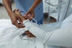 Θηλυκός γιατρός που συνδέει IV σταλαγματιά σε ετοιμότητα θηλυκό υπομονετικό στοκ εικόνες με δικαίωμα ελεύθερης χρήσης