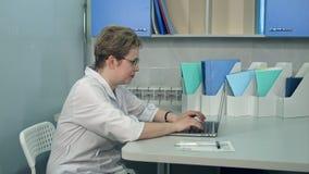 Θηλυκός γιατρός στα γυαλιά που χρησιμοποιούν το φορητό προσωπικό υπολογιστή της στην κλινική Στοκ εικόνα με δικαίωμα ελεύθερης χρήσης