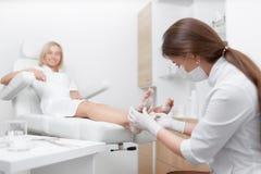 Θηλυκός γιατρός Podiatrist που κάνει τη διαδικασία του μασάζ και του ξεφλουδίσματος Στοκ Φωτογραφίες