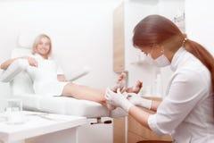 Θηλυκός γιατρός Podiatrist που κάνει τη διαδικασία του μασάζ και του ξεφλουδίσματος Στοκ Εικόνες