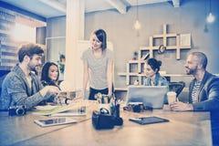 Θηλυκός γραφικός σχεδιαστής που διοργανώνει τη συζήτηση με τους συναδέλφους στοκ εικόνες