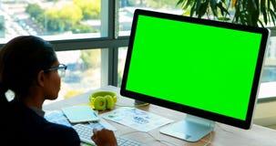 Θηλυκός γραφικός σχεδιαστής που εργάζεται πέρα από τον υπολογιστή στο γραφείο της απόθεμα βίντεο