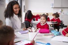 Θηλυκός δάσκαλος και κινεζική συνεδρίαση μαθητριών σε έναν πίνακα σε μια σχολική τάξη νηπίων που χαμογελά σε άλλα παιδιά, εκλεκτι στοκ φωτογραφία