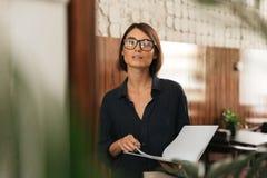 Θηλυκός διευθυντής eyeglasses με τα έγγραφα στα χέρια Στοκ εικόνα με δικαίωμα ελεύθερης χρήσης