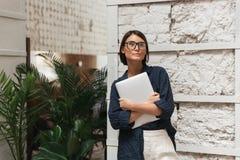 Θηλυκός διευθυντής eyeglasses που κρατά το φάκελλο στα χέρια Στοκ εικόνες με δικαίωμα ελεύθερης χρήσης