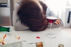 Θηλυκός εθισμός οινοπνεύματος Νέος ύπνος γυναικών στον πίνακα κουζινών που περιβάλλεται με τα μπουκάλια κρασιού στοκ εικόνες με δικαίωμα ελεύθερης χρήσης
