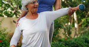 Θηλυκός εκπαιδευτής που βοηθά την ανώτερη γυναίκα στην άσκηση με τους αλτήρες 4k απόθεμα βίντεο