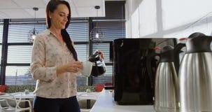 Θηλυκός εκτελεστικός χύνοντας καφές στο φλυτζάνι 4k απόθεμα βίντεο