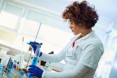 Θηλυκός επιστήμονας που χρησιμοποιεί το σωλήνα δοκιμής με το μπλε υγρό δείγμα Στοκ Εικόνα