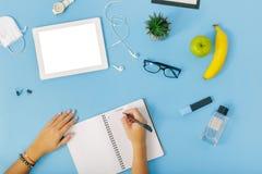 Θηλυκός εργασιακός χώρος Το θηλυκό χέρι τοπ άποψης γράφει το toda σχεδίων σημειωματάριων Στοκ Εικόνες