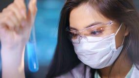 Θηλυκός ιατρικός τεχνικός Ð  Σηάν στα γυαλιά και μάσκα που δημιουργεί την προετοιμασία φαρμακείων στο εργαστήριο φιλμ μικρού μήκους