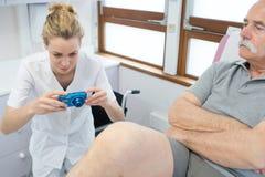 Θηλυκός ιατρός που παίρνει τραυματισμένο το εικόνα πόδι Στοκ Εικόνες