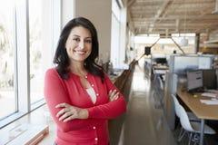 Θηλυκός ισπανικός αρχιτέκτονας που χαμογελά στη κάμερα σε ένα γραφείο στοκ εικόνες