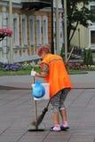 Θηλυκός καθαριστής οδών που σκουπίζει την οδό σε Γκρόντνο Στοκ Φωτογραφίες
