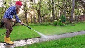 Θηλυκός καθαριστής που εργάζεται στη διάβαση στον κήπο φιλμ μικρού μήκους