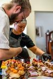 Θηλυκός και αρσενικός αρχιμάγειρας που βάζει τα συστατικά Burgers σε ένα τεμαχισμένο ψωμί που διαδίδεται σε έναν πίνακα στα μαύρα στοκ εικόνες