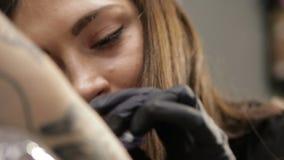 Θηλυκός καλλιτέχνης δερματοστιξιών στο στάδιο της εργασίας, άποψη κινηματογραφήσεων σε πρώτο πλάνο για το πρόσωπο απόθεμα βίντεο