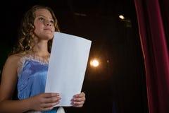 Θηλυκός καλλιτέχνης που διαβάζει τα χειρόγραφά της στη σκηνή στοκ εικόνες