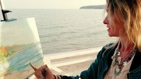 Θηλυκός καλλιτέχνης που χρωματίζει seascape υπαίθρια φιλμ μικρού μήκους