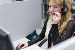 Θηλυκός κεντρικός χειριστής κλήσης που κάνει την εργασία της Στοκ Φωτογραφίες