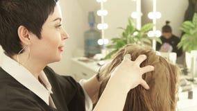 Θηλυκός κομμωτής που κάνει το μασάζ την επικεφαλής νέα γυναίκα hairdressing στο σαλόνι Κλείστε επάνω haircutter να συνεργαστεί με απόθεμα βίντεο