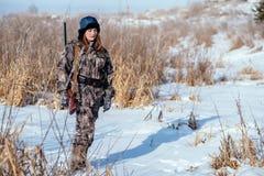 Θηλυκός κυνηγός στα ενδύματα κάλυψης έτοιμα να κυνηγήσουν, κρατώντας το πυροβόλο όπλο α στοκ φωτογραφία με δικαίωμα ελεύθερης χρήσης