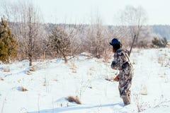 Θηλυκός κυνηγός στα ενδύματα κάλυψης έτοιμα να κυνηγήσουν, κρατώντας το πυροβόλο όπλο α στοκ φωτογραφία