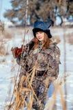 Θηλυκός κυνηγός στα ενδύματα κάλυψης έτοιμα να κυνηγήσουν, κρατώντας το πυροβόλο όπλο α στοκ εικόνες