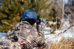 Θηλυκός κυνηγός στα ενδύματα κάλυψης έτοιμα να κυνηγήσουν, κρατώντας το πυροβόλο όπλο α στοκ εικόνα με δικαίωμα ελεύθερης χρήσης