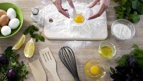 Θηλυκός μάγειρας που προσθέτει το αυγό στο αλεύρι, που προετοιμάζει τη ζύμη για την κατασκευή των σπιτικών τηγανιτών Στοκ Φωτογραφίες