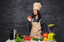 Θηλυκός μάγειρας στον πίνακα που προετοιμάζει τα vegan γεύματα Στοκ Εικόνες