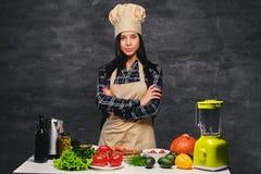 Θηλυκός μάγειρας στον πίνακα που προετοιμάζει τα vegan γεύματα Στοκ Εικόνα