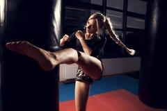 Θηλυκός μαχητής που χτυπά τη βαριά τσάντα με το πόδι της Στοκ φωτογραφία με δικαίωμα ελεύθερης χρήσης