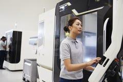 Θηλυκός μηχανικός που ενεργοποιεί CNC τα μηχανήματα στο εργοστάσιο στοκ φωτογραφίες