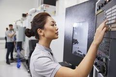 Θηλυκός μηχανικός που ενεργοποιεί CNC τα μηχανήματα στο εργοστάσιο στοκ φωτογραφία με δικαίωμα ελεύθερης χρήσης