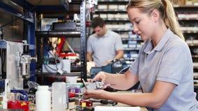Θηλυκός μηχανικός στο εργοστάσιο που μετρά το συστατικό στον πάγκο εργασίας που χρησιμοποιεί το μικρόμετρο